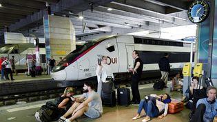 Des voyageurs attendent à la gare Montparnasse, le 27 juillet 2018 à Paris. (GERARD JULIEN / AFP)