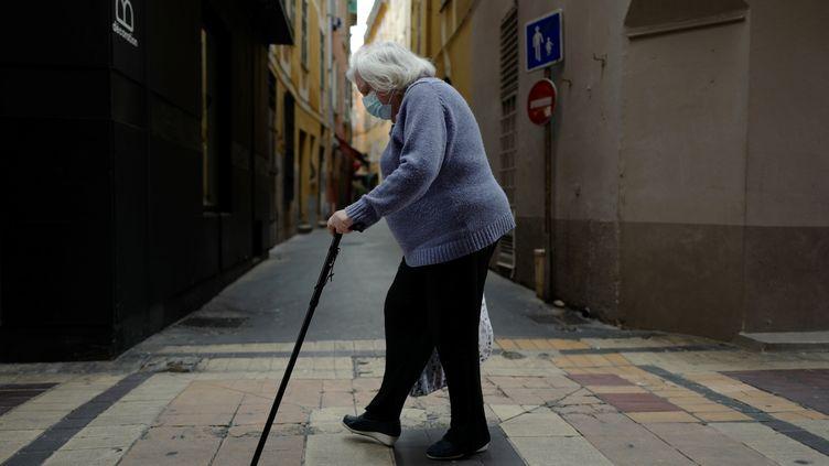 Une personne agée traverse une rue, portant son masque. Photo d'illustration. (VALERY HACHE / AFP)