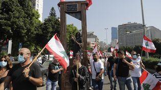 Des manifestants défilent à Beyrouth avec une guillotine pour dénoncer la corruption des dirigeants du Liban, le 4 août 2021, un an après les explosions qui ont dévasté une partie de la capitale. (JOSEPH EID / AFP)