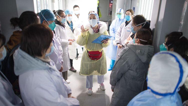 Une infirmière assigne les tâches de la journée avant l'accueil de malades du Covid-19, le 8 février 2020 à l'hôpital de Wuhan (Chine). (XIAO YIJIU / XINHUA / AFP)