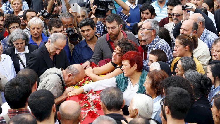 Des proches des victimes de l'attentat d'Ankara (Turquie) se recueillent sur le cercueil de l'une d'entre elles, le 11 octobre 2015. (UMIT BEKTAS / REUTERS)