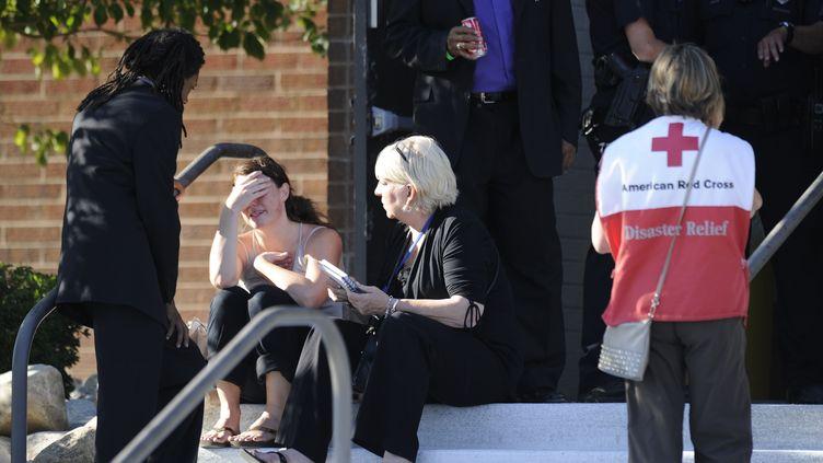Femme en pleurs devant une école d'Aurora (Colorado, Etats-Unis), où sont réunies les familles des victimes du tireur qui a fait12 morts et une quarantaine de blessés jeudi 19 juillet dans un cinéma. (JONATHAN CASTNER / AFP)