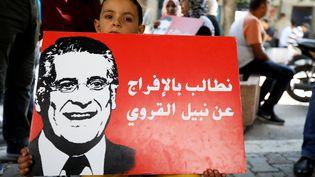 """Un gamin tient une affiche du candidat Nabil Karoui lors d'une manifestation de soutien à l'homme d'affaires emprisonné pour """"blanchiment"""", le 3 septembre 2019 à Tunis. (ZOUBEIR SOUISSI / X02856)"""