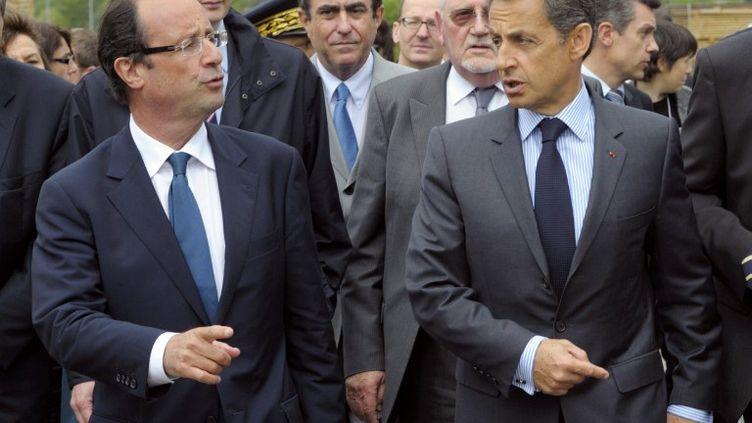 François Hollande, candidat socialiste à la présidentielle de 2012, et le président de la République Nicolas Sarkozy, à Egletons (Corrèze), le 27 avril 2011. (PHILIPPE WOJAZER / AFP)