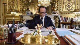 François Hollande assis à son bureau, au palais de l'Elysée, le 24 février 2015. (ERIC FEFERBERG / POOL)