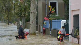 Des pompiers secourent des habitants de Trèbes, près de Carcassonne (Aude), le 15 octobre 2018. (PASCAL PAVANI / AFP)