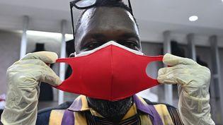 Le créateur de mode ivoirien Roger Bango présente un masque de fabrication artisanale réalisé dans son atelier à Abidjan, le 9 avril 2020. (ISSOUF SANOGO / AFP)