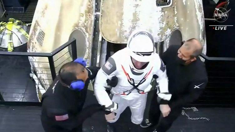 Capture d'écran du direct de la Nasa, le 2 mai 2021, montrant un membre de l'équipage du vaisseau spatial SpaceX sortant de la capsule après son retour sur Terre, au large de Panama City, en Floride. (NASA / AFP)