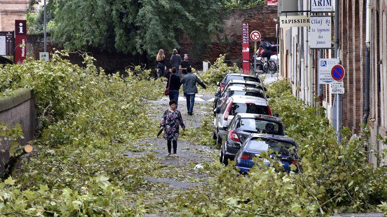 Les gens marchent sur les branches tombées dans les rues de Montauban, le 1er septembre 2015. (PASCAL PAVANI / AFP)