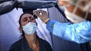 Une femme testée pour le Covid-19 dans un laboratoire à Paris, le 4 septembre 2020. (CHRISTOPHE ARCHAMBAULT / AFP)