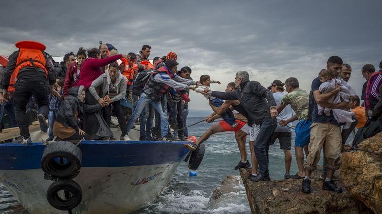 Des migrants arrivent sur l'île grecque de Lesbos à bord d'un bateau de pêche, le 11 octobre 2015. (ANTONIO MASIELLO / NURPHOTO / AFP)