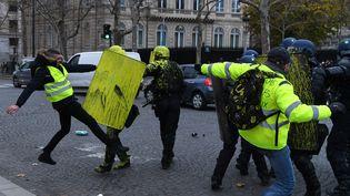 """Des """"gilets jaunes"""" s'opposent aux forces de l'ordre à Paris, aux abords des Champs-Elysées. (ALAIN JOCARD / AFP)"""