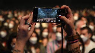 Un spectateur prend une photo avant le début du concert-test au Palau Sant Jordi de Barcelone, le 27 mars 2021. (LLUIS GENE / AFP)