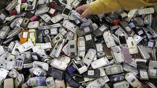 Un ouvrier d'une usine de recyclage de Tokyo (Japon) saisit un téléphone portable au milieu de vieux mobiles. (TORU HANAI / REUTERS)