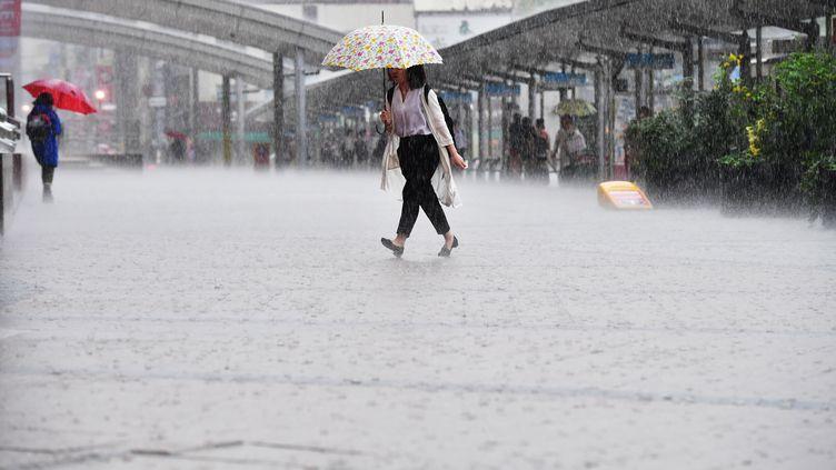 Une passante affronte les intempéries à Kagoshima (Japon), le 3 juillet 2019. Cette ville de près de 600 000 habitants fait partie des zones concernées par l'ordre d'évacuation. (SHOHEI IZUMI / YOMIURI / AFP)