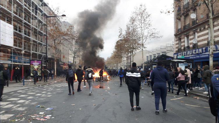Des poubelles et autres meubles trouvés dans la rue brûlent sur la chaussée. Plusieurs centaines de jeunes sont rassemblésà Aubervilliers (Seine-Saint-Denis), lundi 3 décembre. (RADIO FRANCE / REMI BRANCATO)