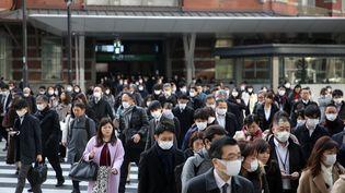 Des personnes portant des masques pour se protéger du coronavirus Covid-19, le 25 février 2020 à Tokyo (Japon). (KUNIHIKO MIURA / YOMIURI / AFP)