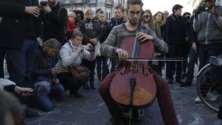 Un homme joue du violoncelle au mémorial improvisé place de la Bourse à Bruxelles, après les attentats qui ont touché la capitale belge mardi 22 mars 2016. (KENZO TRIBOUILLARD / AFP)