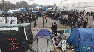 """Des migrants font la queue à l'entrée d'un hangar, dans lequel ils sont orientés, pendant l'évacuation de la """"jungle"""" de Calais, le 24 octobre 2016, à Calais. (FRANCOIS LO PRESTI / AFP)"""