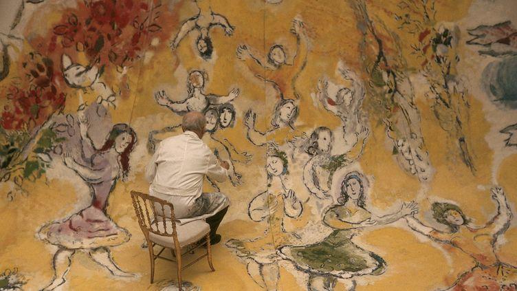 Détail d'un cliché du photographe Izis montrant Marc Chagall en 1964 au travail sur le plafond de l'Opéra de Paris. Ici, la partie du panneau concernant Mozart, le compositeur préféré du peintre.  (ADAGP Paris. Photo Izis-Bidermanas)