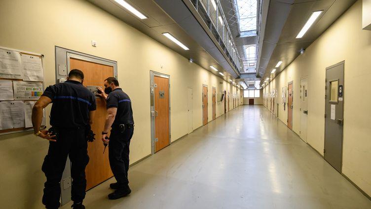 Des gardiens de prison ferment une porte dans un couloir de la prison de la Sante à Paris, le 6 novembre 2020. Photo d'illustration. (BERTRAND GUAY / AFP)