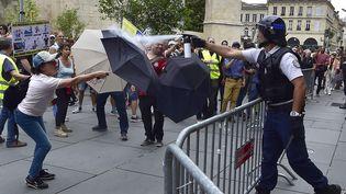 """BORDEAUX. En France, comme ici à Bordeaux, la situation s'est parfois tendue dans les cortèges.Cettemanifestante se protège d'un spray au poivre utilisé par un policier en marge d'une marche pour le climat à laquelle se sont mêlés des """"gilets jaunes"""", le 21 septembre 2019. (GEORGES GOBET / AFP)"""