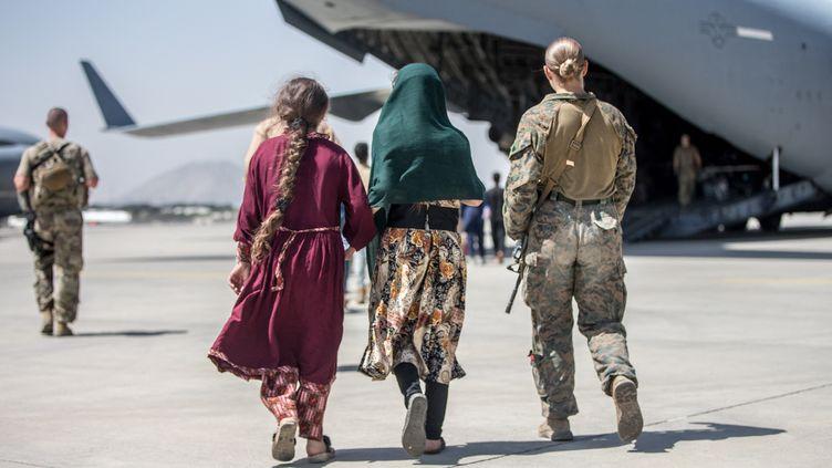 Une militaire de l'armée américaine escorte des enfants durant une opération d'évacuation à l'aéroport Hamid Karzai, à Kaboul (Afghanistan), le 24 août 2021. (EYEPRESS NEWS / AFP)