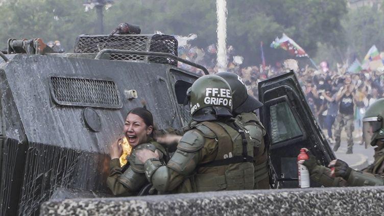 Une policière a été brûlée lors des affrontements lundi 4 novembre 2019 à Santiago (Chili). (PABLO COZZAGLIO / AFP)