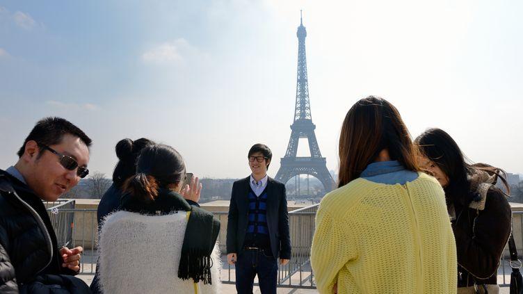 Un groupe de touristes chinois pose devant la tour Eiffel, le 27 mars à Paris. (ERIC FEFERBERG / AFP)