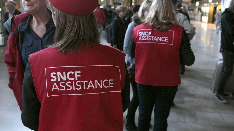 Des employés de la SNCF conseillent des voyageurs à Paris, lors d'une grève du 7 octobre 2011. (JACQUES DEMARTHON / AFP)
