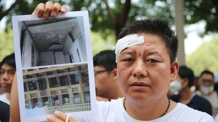 (Un habitant de Tianjin qui vivait dans un immeuble abîmé par l'explosion mercredi, montre des photos de son foyer détruit devant l'hôtel Meihua © MAXPPP)