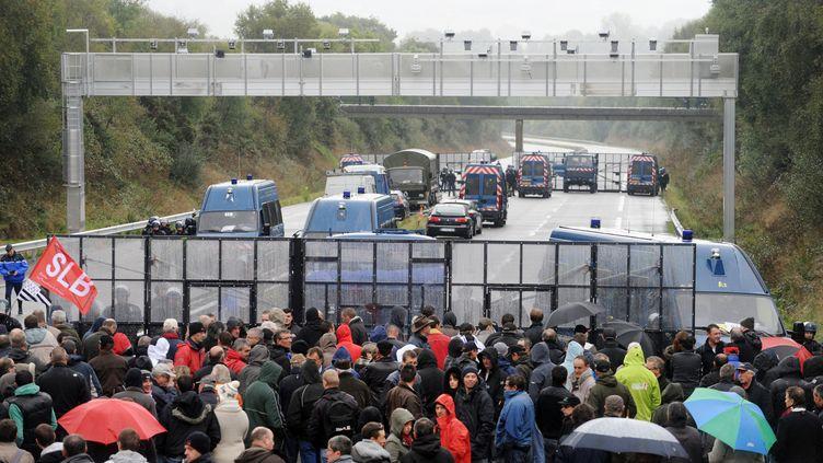 Des gendarmes français et des manifestants contre l'écotaxe autour du portique dePont-de-Buis-lès-Quimerch (Finistère), le 12 octobre 2013. (FRED TANNEAU / AFP)