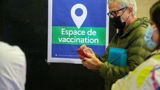 Un homme consulte son téléphone dans un centre de vaccination, le 16 avril 2021 à Crest (Drôme). (NICOLAS GUYONNET / HANS LUCAS / AFP)