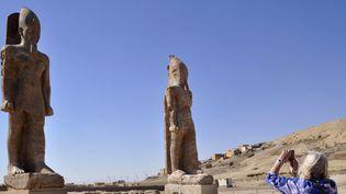 Une touriste prend une photo des 2 statues du pharaon Amenhotemp III, au temple de Louxor, le 14/12/2014  (RADWAN ABU-ELMAGD / AFP)