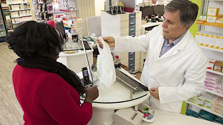 Un pharmacien s'entretient avec une cliente, le 17 avril 2014. (CHASSENET / BSIP)
