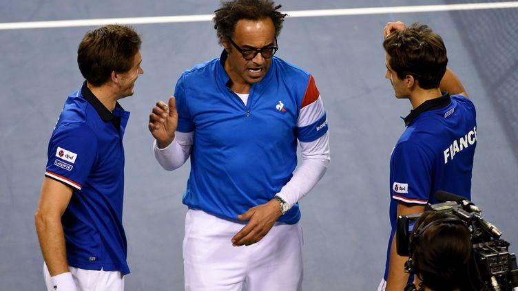 Le capitaine de l'équipe de France de tennis Yannick Noah entouré deNicolas Mahut et dePierre-Hugues Herbert le 4 février 2017 à Tokyo. (TORU YAMANAKA / AFP)