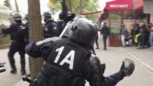 Une vidéo devenue virale montre un CRS s'emparant d'un pavé pour le jetervers les manifestants, à Paris, en marge des manifestationsdu 1er-Mai (capture d'écran). (LINE PRESS)
