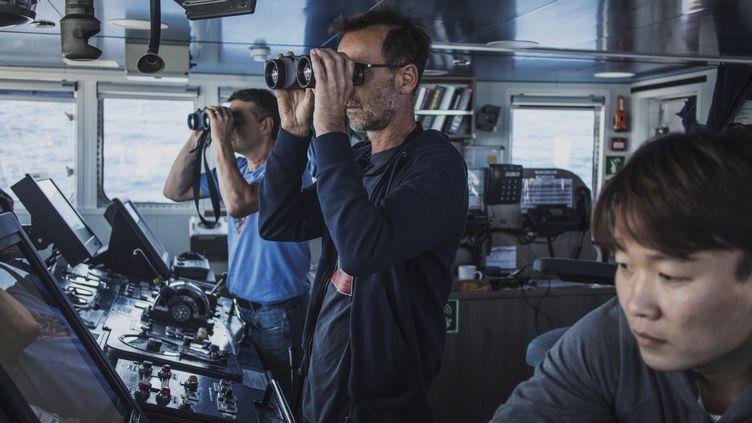 """En direction du mont sous-marin Vema (Afrique du Sud), l'océanographe de Greenpeace Thilo Maack (à gauche) et le capitaine de l'""""Arctic Sunrise"""" Mike Flnchen regardent le large àla jumelle, le 30 octobre 2019. (MARCO LONGARI / AFP)"""