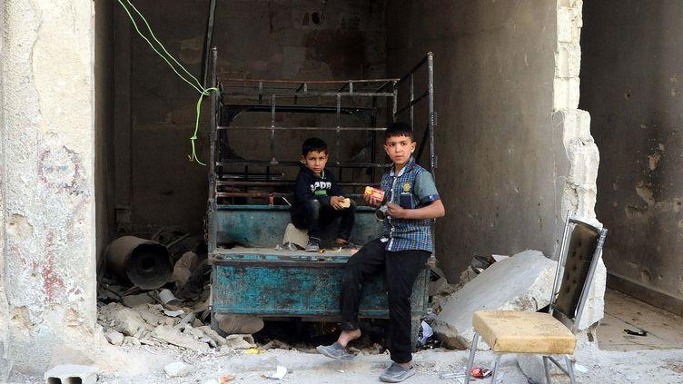 Des Syriens devant un bâtiment détruit de la ville de Zamalka dans la Ghouta (Syrie), le 4 avril 2018. (CHINE NOUVELLE/SIPA/XINHUA)