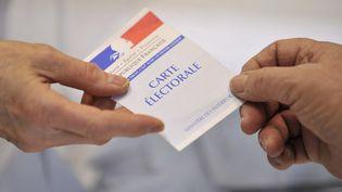 Un électeur présente sa carte électorale le 14 mars 2010. (THIERRY ZOCCOLAN / AFP)