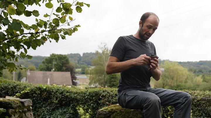 Assis sur un muret, Mathias Dolidon cherche à capter le réseau mobile à Brassy (Nièvre). (PIERRE-LOUIS CARON / FRANCEINFO)