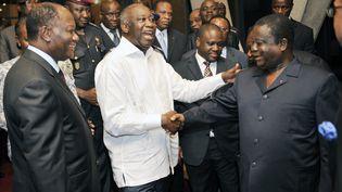Au centre, Laurent Gbagbo (en blanc) et Henri Konan Bédié échangent une poignée de main au palais présidentiel le 30 juin 2010, à Abidjan (Côte d'Ivoire), sous les yeux d'Alassane Ouattara (à gauche) et en présence de Guillaume Soro (à droite de Laurent Gbagbo). (SIA KAMBOU / AFP)