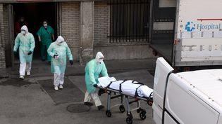 Des soignants évacuent un corps, le 25 mars 2020 à l'hôpital Gregorio Maranon de Madrid (Espagne). (OSCAR DEL POZO / AFP)