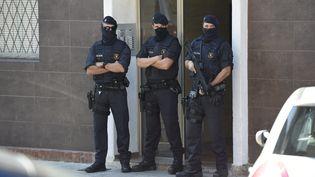 Des membres desMossos d'Esquadra, la polie régionale catalane, devant l'appartement du suspect ayant attaqué un commissariat à Cornellà de Llobregat (Catalogne, Espagne), le 20 août 2018. (LLUIS GENE / AFP)