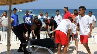 Des secouristes transportent un corps recouvert, vendredi 26 juin 2015 à Sousse (Tunisie). Au moins 37 personnes sont mortes dans une fusillade. (BECHIR TAIEB / AFP)