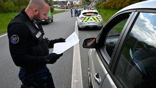 Un gendarme contrôle l'attestation de déplacement dérogatoire d'un automobiliste, le 3 avril 2020, à Bréal-sous-Montfort (Ille-et-Vilaine). (DAMIEN MEYER / AFP)