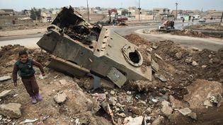 Dans un quartier est de Mossoul, le 21 janvier 2017, un enfant se tient près d'un véhicule détruit par les affrontements entre les forces irakiennes et Daesh (AHMAD AL-RUBAYE / AFP)