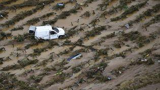 Une voiture au milieu d'un champ, le 15 octobre 2018, près de Villegailhenc (Aude), après des inondations dévastatrices. (SYLVAIN THOMAS / AFP)