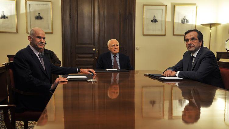 Les négociations pour composer un gouvernement de coalition en Grèce, avec le premier ministre sortant George Papandréou (à gauche), le président Carolos Papoulias (au centre) et le chef de l'opposition Antonis Samaras (à droite), le 6 novembre 2011 à Athènes. (AFP PHOTO / LOUISA GOULIAMAKI)