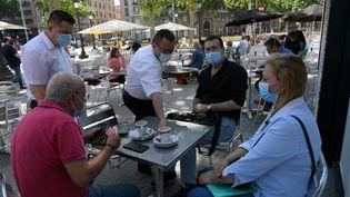 Des clients masqués à la terrasse d'un bar sur les Ramblas de Barcelone (Espagne), le 25 mai 2020 (LLUIS GENE / AFP)